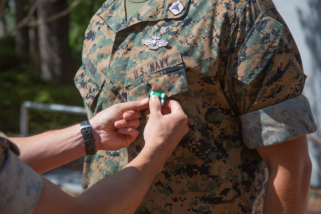 """U.S. Navy Corpsman HM1 Michael D. Bryson, a corpsman with 1st Battalion 8th Marine Regiment, receives a Navy Commendation Medal during an award ceremony at Camp Lejeune, N.C., September 22, 2020. Bryson received the Chief Hospital Corpsman George William """"Doc"""" Piercy award (not pictured), which recognizes one Navy corpsmen who has earned the Fleet Marine Force (FMF) badge for contributing to the combat readiness of any air or ground element in the Marine Corps. Bryson also received a Navy Commendation Medal for his outstanding service and accomplishments while serving as a corpsman for 1st Battalion 8th Marine Regiment. (U.S. Marine Corps photo by Lance Cpl. Nicholas Guevara)"""