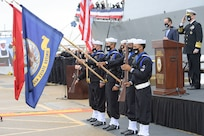 The USS Cole Color Guard parades the colors during the National Anthem at the Arleigh Burke-class guided missile destroyer USS Cole (DDG 67) 20th Anniversary memorial ceremony at Naval Station Norfolk.