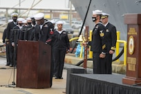 Gas Turbine Systems Technician (Mechanical) 1st Class Quazavier Henderson honors Engineman 2nd Class Marc Nieto during roll call at the Arleigh Burke-class guided missile destroyer USS Cole (DDG 67) 20th Anniversary memorial ceremony at Naval Station Norfolk.