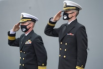 Cmdr. Edward Pledger, commander, USS Cole (DDG 67) and Lt. j.g. Harry Hazell, Chaplin, USS Cole, salutes during the National Anthem at the Arleigh Burke-class guided missile destroyer USS Cole (DDG 67) 20th Anniversary memorial ceremony at Naval Station Norfolk.