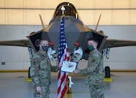 U.S. Air Force Col. Matthew Powell, the 354th Maintenance Group commander, awards Tech. Sgt. Theodore Crowely, III, a 354th Aircraft Maintenance Squadron F-35A Lightning II dedicated crew chief (DCC), the title of DCC on Eielson Air Force Base, Alaska, Oct. 9, 2020. The purpose of the DCC program is to provide continuity and accuracy by assigning ownership of each aircraft to a maintainer. (U.S. Air Force photo by Senior Airman Beaux Hebert)