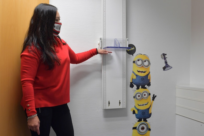 A woman standing next to a height measurement ruler.