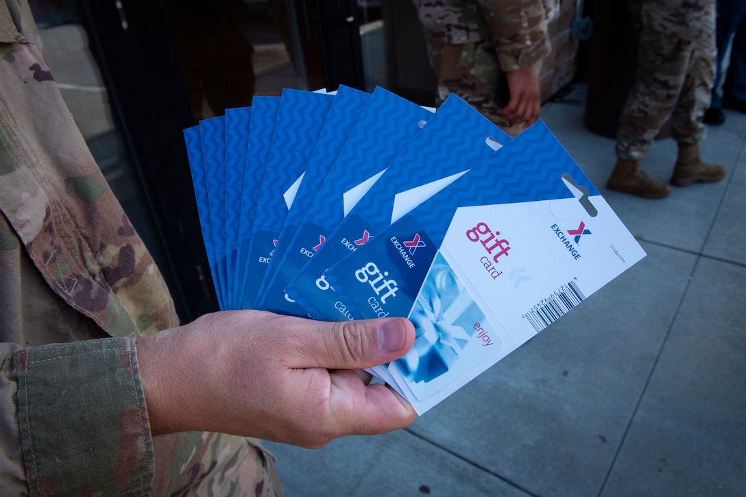 A photo of a sergeant holding gift cards.