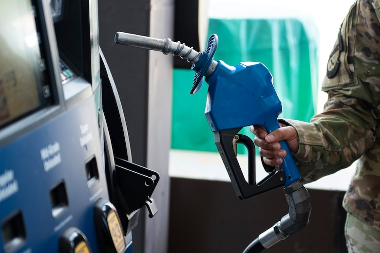 A photo of an Airman grabbing a gas pump.