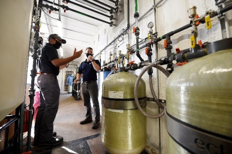 Brad Geisman, left, pilot engineer, and Dan Casey, lead field operations engineer for Emerging Compounds Treatment Technologies (ECT2), discuss the patented regenerable ion exchange (SORBIX RePURE) water  treatment system being used to remove per- and polyfluoroalkyl substances (PFAS) from groundwater at the fire training area of Wright-Patterson Air Force Base, Ohio on Sept. 29, 2020.  U.S. Air Force personnel from the Air Force Civil Engineer Center are leading the study of combining proven remediation techniques that can remove PFAS with new destruction technologies to  destroy the PFAS. PFAS are a group of chemicals, some of which were formerly used in aircraft fire fighting foam. (U.S. Air Force photo by Ty Greenlees)