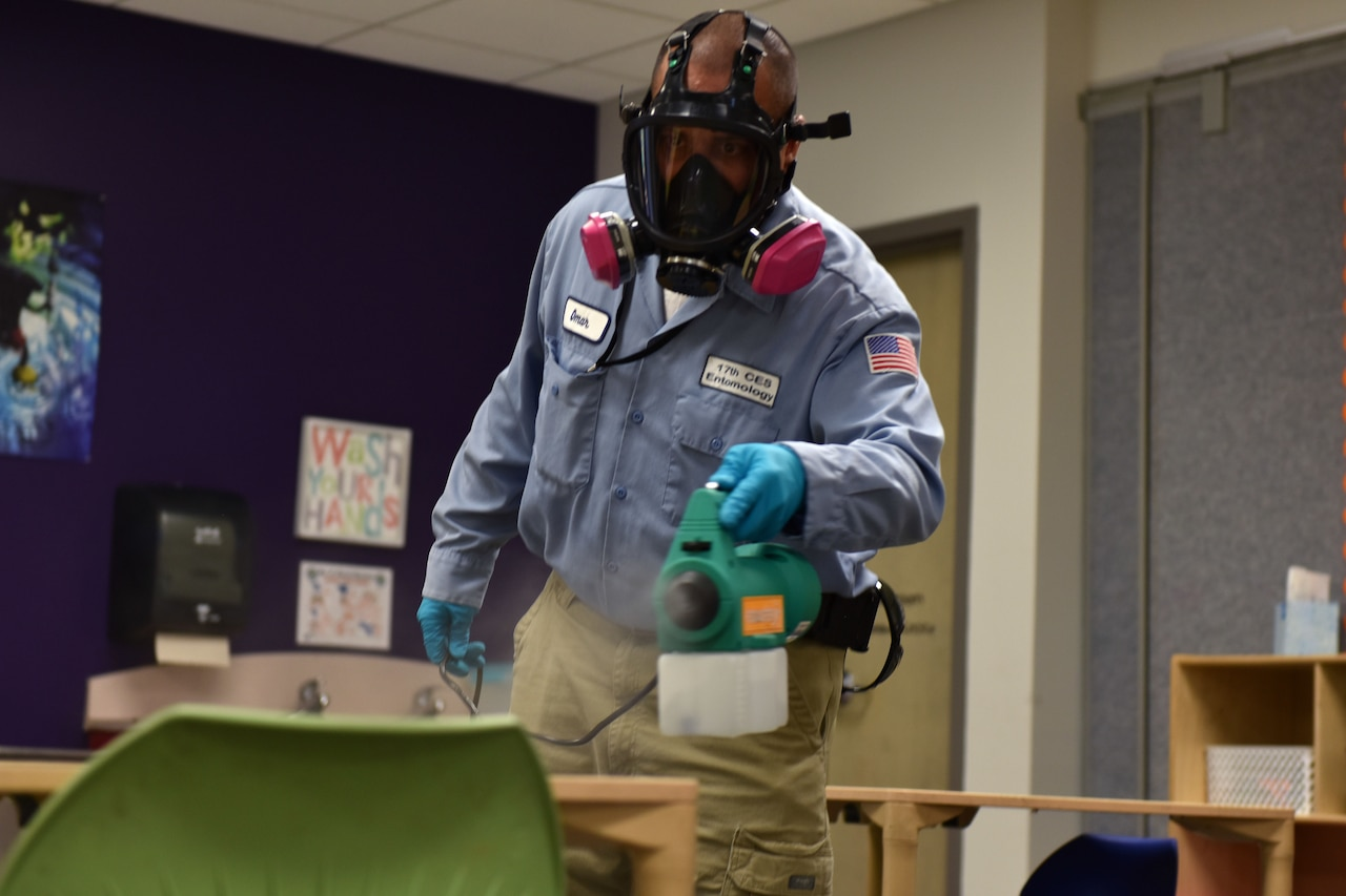 A man dressed in a protective mask and gloves sprays a mist onto a desk.