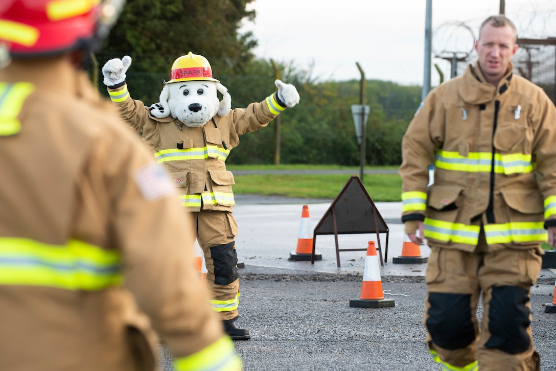 Sparky the Fire Dog and 423rd Civil Engineer Squadron firefighters welcome drivers to RAF Molesworth, England, Oct. 6, 2020 during Fire Prevention Week 2020. Sparky was created for the National Fire Protection Association in 1951 to teach children and adults about fire safety. (U.S. Air Force photo by Senior Airman Jennifer Zima)