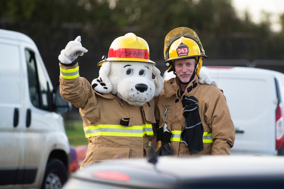 Sparky the Fire Dog and Bob Ratcliffe, 423rd Civil Engineer Squadron firefighter, pose for a photo at RAF Molesworth, England, Oct. 6, 2020 during Fire Prevention Week 2020. Since 1922, national Fire Prevention Week is intended to educate the public about the importance of pre-planning actions they should take to keep themselves and their families safe from fire mishap. (U.S. Air Force photo by Senior Airman Jennifer Zima)