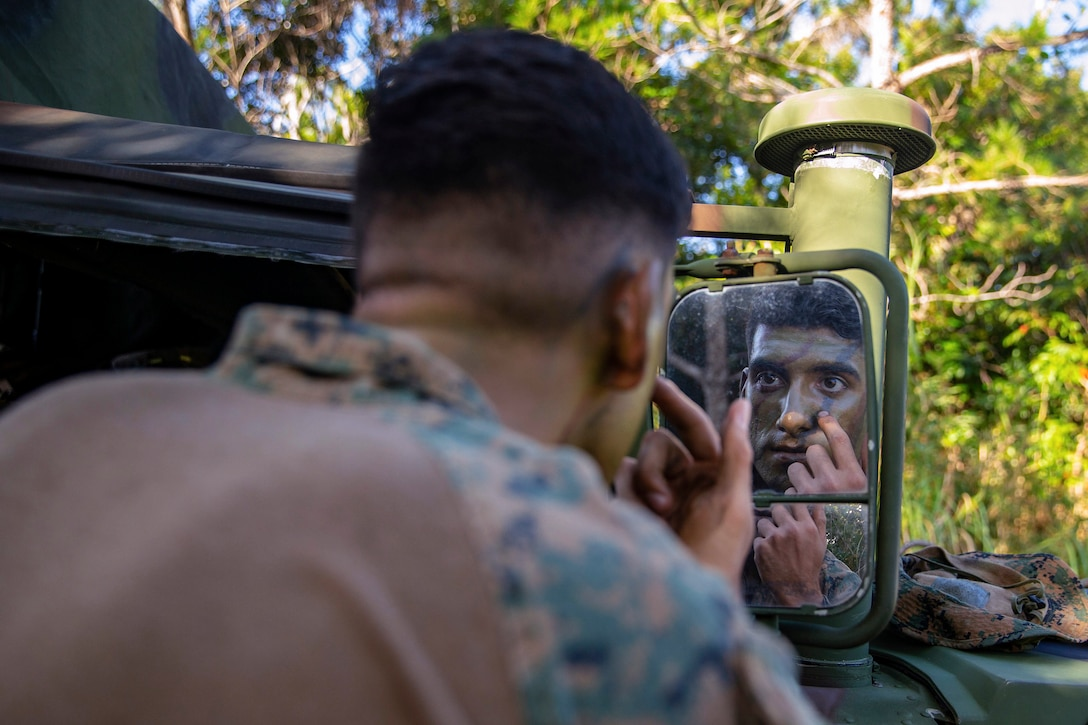 A Marine puts on camouflage paint on his face while looking in the mirror.