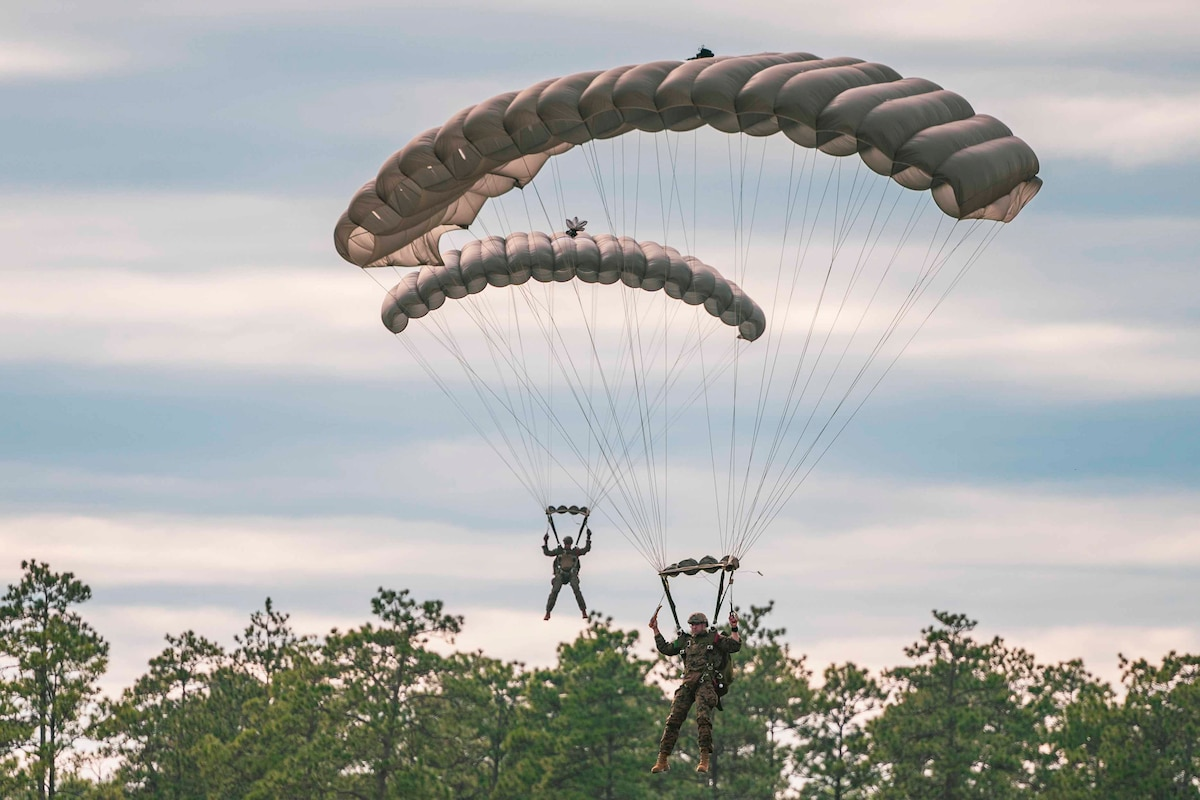 Two Marines descend in the sky wearing parachutes.