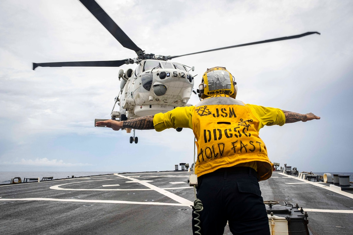A sailor standing on a ship's deck signals a helicopter about to land on the ship.