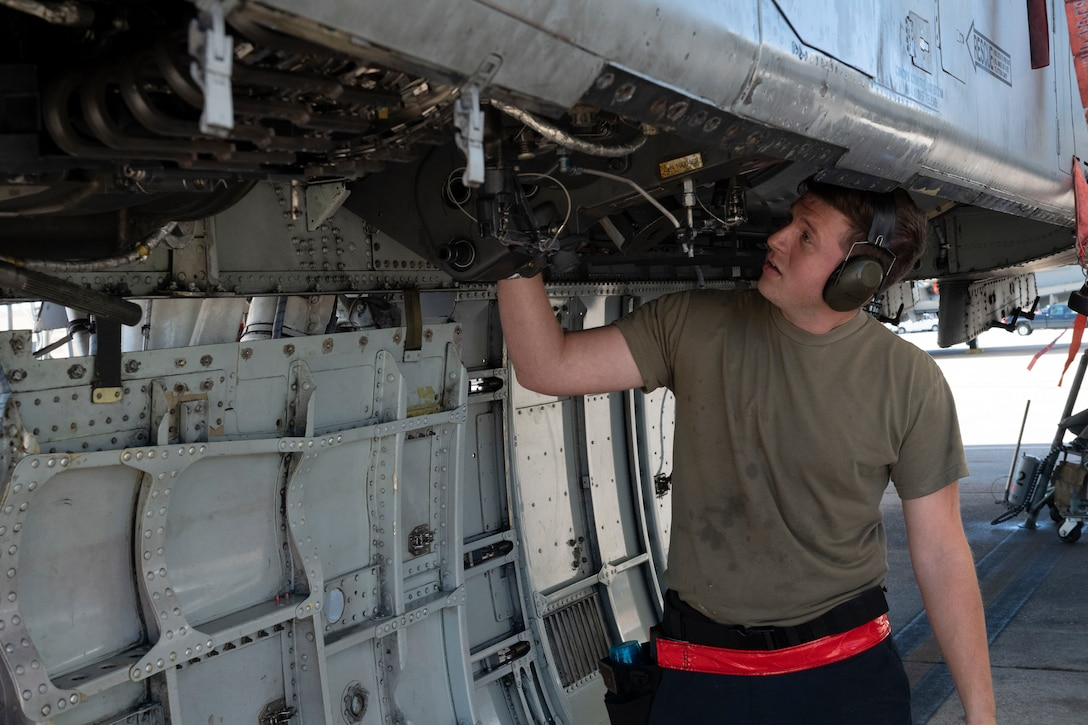 A photo of an Airman installing a GAU-8 Avenger 30 mm cannon ammunition element on an A-10C Thunderbolt II.