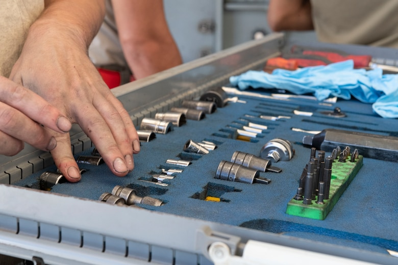 A photo of an Airman selecting a tool from a toolbox.