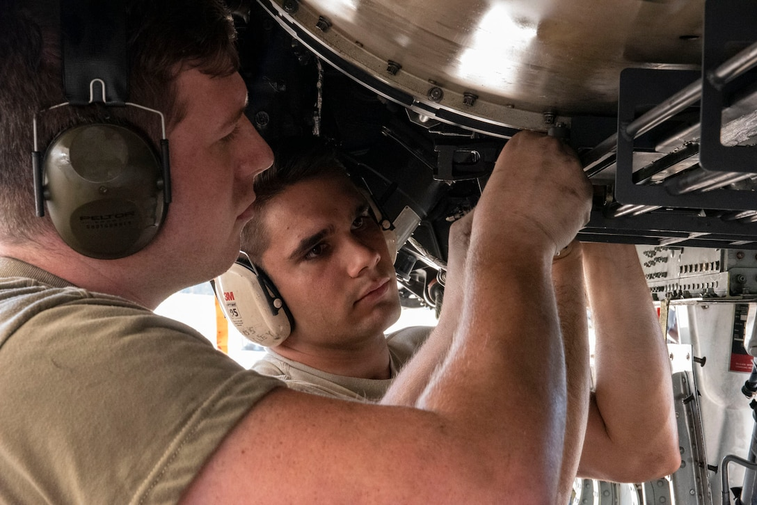 A photo of Airmen installing the GAU-8 Avenger 30 mm cannon's timing gears on an A-10C Thunderbolt.