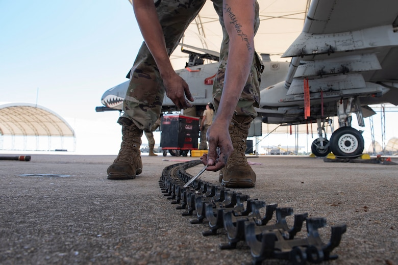 A photo of an Airman counting conveyer elements before they are loaded into the GAU-8 Avenger 30 mm cannon on an A-10C Thunderbolt II
