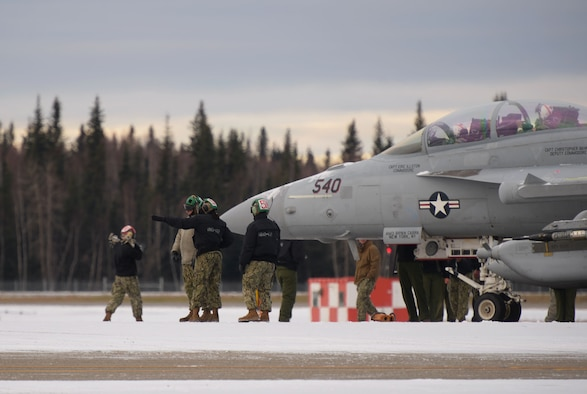 U.S. Navy aircraft mechanics assigned to the Electronic Attack Squadron (VAQ) 132 perform maintenance on an EA-18G Growler during RED FLAG-Alaska 21-1 on Eielson Air Force Base, Alaska, Oct. 13, 2020. RED FLAG-Alaska exercises are designed to provide training for deployed aircrew, maintenance and support personnel in sustainment of large-force deployed air operations. (U.S. Air Force photo by Senior Airman Beaux Hebert)