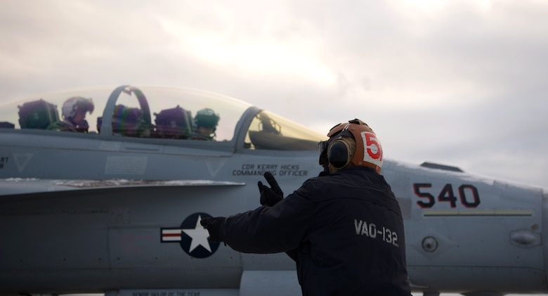 A U.S. Navy aircraft mechanic assigned to the Electronic Attack Squadron (VAQ) 132 marshals an EA-18G Growler during RED FLAG-Alaska 21-1 on Eielson Air Force Base, Alaska, Oct. 13, 2020. The EA-18G is an advanced airborne electronic attack aircraft, capable of operating from an aircraft carrier as well as land-bases. (U.S. Air Force photo by Senior Airman Beaux Hebert)