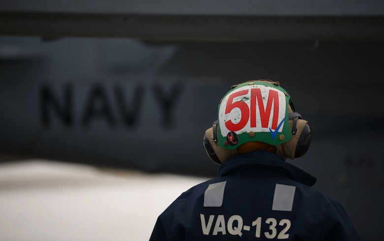 U.S. Navy aircraft mechanic assigned to the Electronic Attack Squadron (VAQ) 132 inspects an EA-18G Growler prior to launch during RED FLAG-Alaska 21-1 on Eielson Air Force Base, Alaska, Oct. 13, 2020. RED FLAG-Alaska provides unique opportunities to integrate various forces into joint training from simulated forward operating bases. (U.S. Air Force photo by Senior Airman Beaux Hebert)