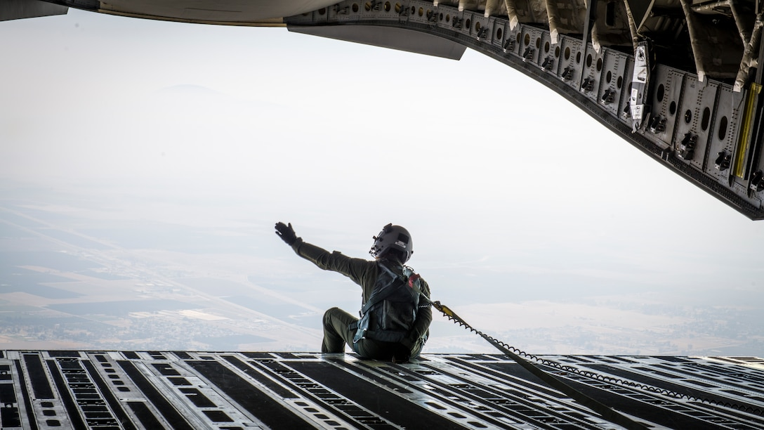 Staff Sgt. Kori Myers, 418th Flight Test Squadron C-17 load master, waves from the back of a C-17 Globemaster III during the 2020 Aerospace Valley Air Show at Edwards Air Force Base, Oct. 9. (Air Force photo by Giancarlo Casem)