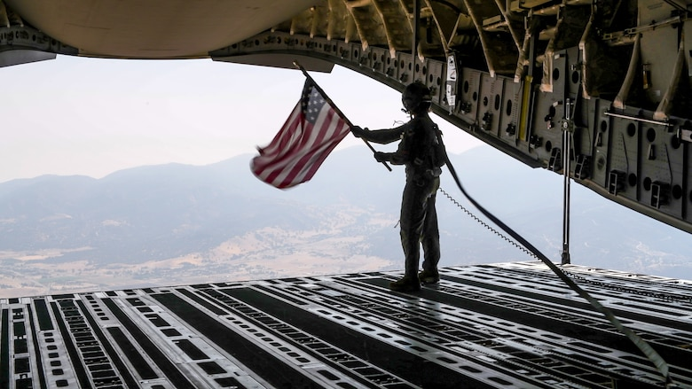 Staff Sgt. Kori Myers, 418th Flight Test Squadron C-17 load master, waves the U.S. flag from the back of a C-17 Globemaster III during the 2020 Aerospace Valley Air Show at Edwards Air Force Base, Oct. 9. (Air Force photo by Giancarlo Casem)