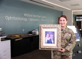 Tech. Sgt. Christine R. Narro, 433rd Aerospace Medicine Squadron, an enlisted Reserve Citizen Airman with the 433rd Airlift Wing at Joint Base San Antonio–Lackland, Texas, holds a picture frame of her grandfather, Felix Gonzalez and grandmother, Josefina, in the lobby of Wilford Hall Eye Center. This is the location where she works as an Optometry Technician during her Unit Training Assemblies on her weekend duty.  (U.S. Air Force photo by Tech. Sgt. Iram Carmona)