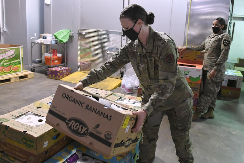 Airman Sara Mark, 194th Wing student flight, packs boxes of food at the Nourish Pierce County warehouse in Lakewood, Washington Sept. 2, 2020. Airmen and soldiers from the Washington National Guard have been working at the warehouse since early April as part of the states Covid-19 response efforts. (Air National Guard photo by Master Sgt. Chacon)