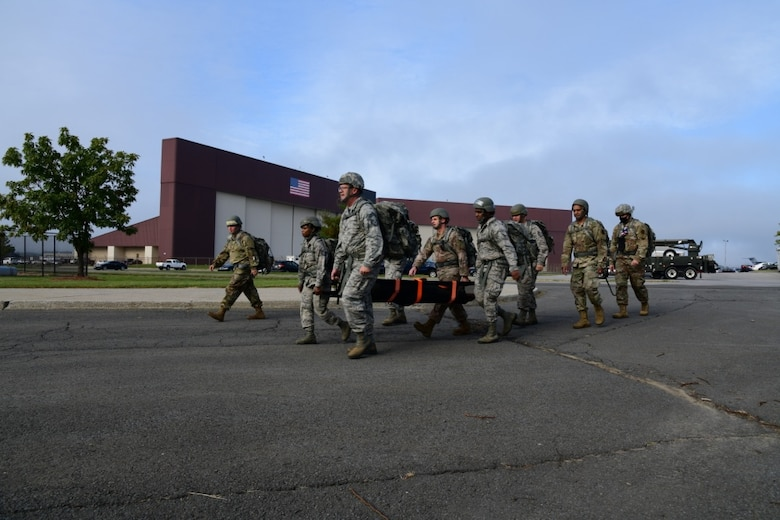 Members of the 105th Airlift Wing Logistics Readiness Squadron conduct a ruck march as a part of a unit cohesion exercise, October 4, 2020, at Stewart Air National Guard Base, Newburgh, NY. Airmen simulated that they were rescuing a downed pilot and set off to complete the mission with their equipment and a stretcher. (U.S. Air Force photo by Senior Airman Jonathan Lane)
