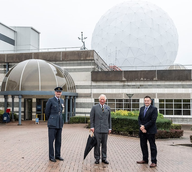 His Royal Highness, center, the Prince of Wales poses for a photo along with Squadron Leader Geoff Dickson, left, RAF Commander for RAF Menwith Hill and Mr Gav Smith, Director General of Technology, Government Communications Headquarters, at RAF Menwith Hill, England, Oct. 12, 2020. (Courtesy Photo)