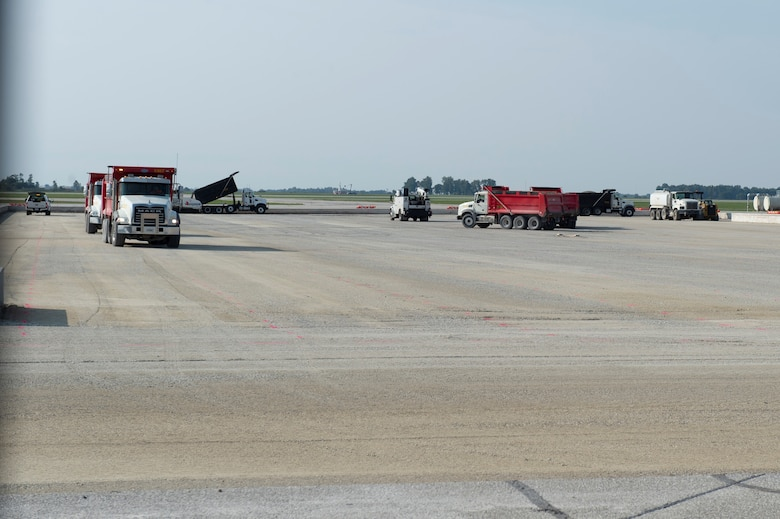 Dump trucks remove old concrete from the flightline at Grissom Air Reserve Base, Indiana, Sept. 23, 2020. The part of the flightline needed to be replaced as part of its routine structural maintenance. (U.S. Air Force photo by Staff Sgt. Michael Hunsaker)