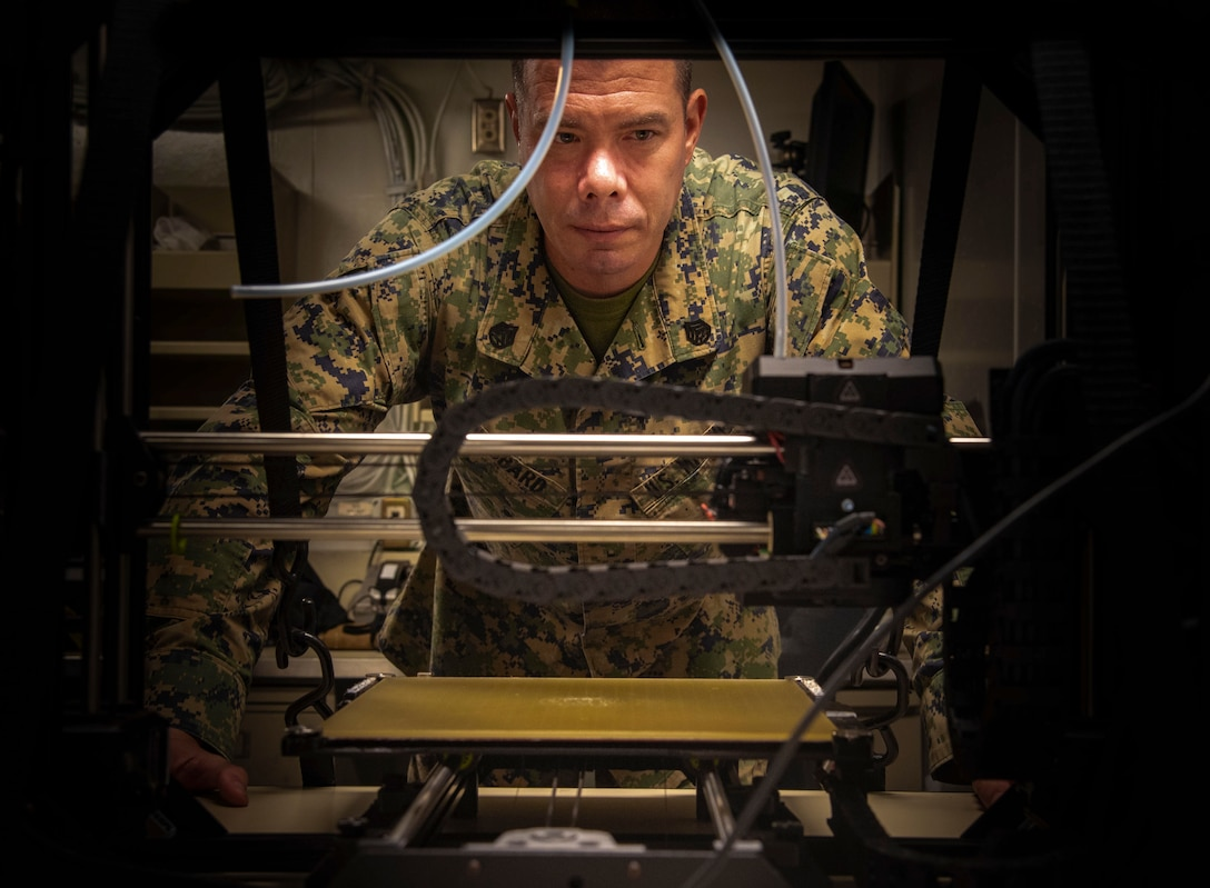 A U.S. Marine observes a 3D printer as it prints an equipment part used aboard USS New Orleans (LPD 18), Aug. 24.