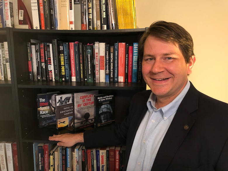 Dr. Nicholas Sambaluk, Air Command and Staff College associate professor of strategy and director of research at the eSchool of Graduate Professional Military Education, poses near a book case.