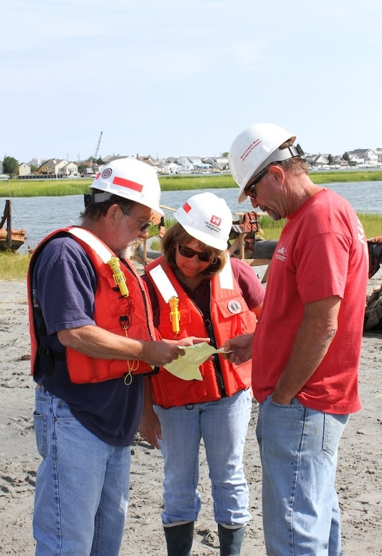 Monica Chasten (middle) discusses dredging and placement operations with USACE Inspector Charlie Yates (left) and Joe Hill (right), owner of Barnegat Bay Dredging Company. The U.S. Army Corps of Engineers has partnered with the state of New Jersey and several non-profit organizations on a dredging and marsh restoration project along the New Jersey Intracoastal Waterway. The demonstration project involves dredging critical shoals from the waterway and restoring ecological habitat.