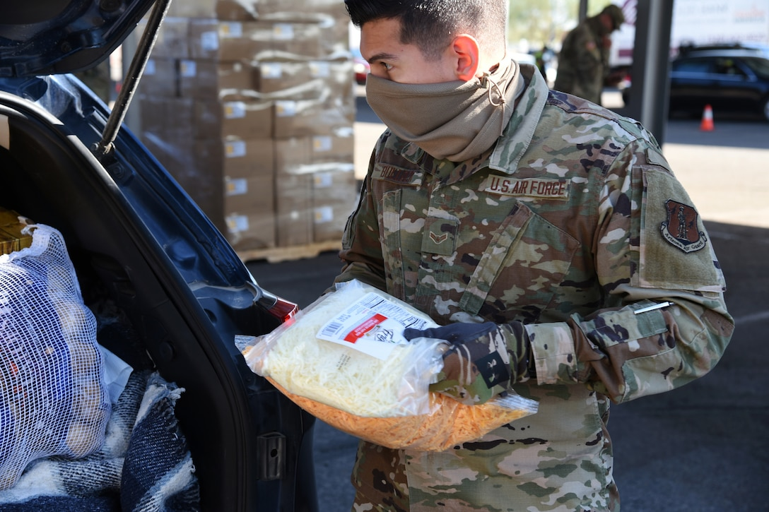 An airman wearing a face mask and gloves loads groceries into a vehicle.