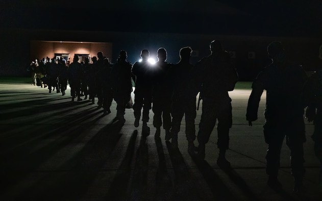 Airmen stand out on the flightline awaiting deployment.
