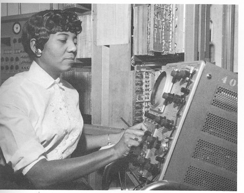 Black and white picture of Dorothy B. John  checking information on a digital differential analyzer.