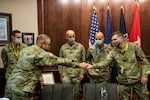 Indiana National Guard Brig. Gen. Dale Lyles, the adjutant general, gives a challenge coin to 2nd Lt. Blaine Zimmerman, Indianapolis, Wednesday, Oct. 7, 2020. Zimmerman, along with 1st Sgt. Joe McFarren, Liberty Center; Staff Sgt. Whitney Lake, Indianapolis; Lt. Col. Jason Doffin, Carmel, and 1st Lt. Gary Parks, Camby, earned sport on the All-Guard Marathon Team in September during time trails in Nebraska.