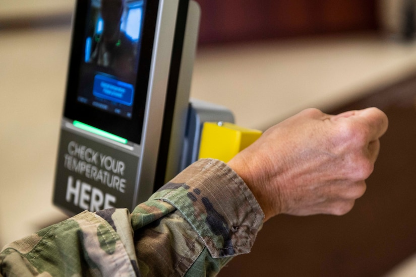A soldier holds their wrist up to a scanner to be scanned.