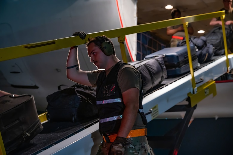 An Airmen helps load luggage onto the plane.