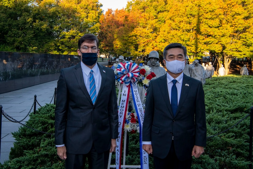Men stand beside a wreath.