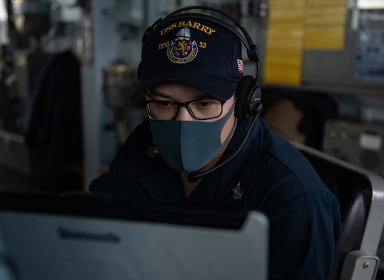 Operations Specialist 1st Class Jose Gonzalez looks for contacts on the Automated Information System (AIS) laptop while standing watch aboard the Arleigh-Burke class guided missile destroyer USS Barry (DDG 52).