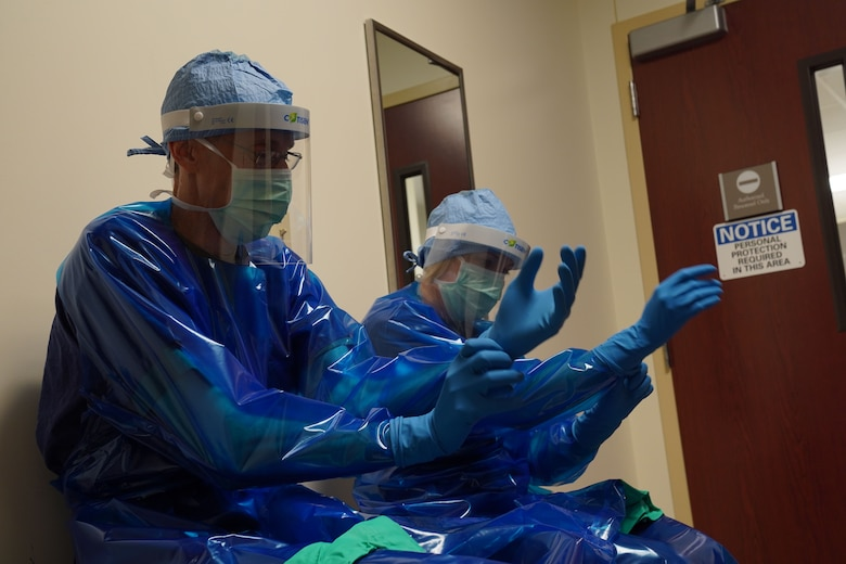 U.S. Air Force Col. Kirsten Aguilar, Joint Base Elmendorf-Richardson and 673d Air Base Wing commander, and U.S. Air Force Chief Master Sgt. Lee Mills, JBER and 673d ABW command chief, don protective gear before participating in the sterilization process for 673d Surgical Operations Squadron's surgical instruments during a 673d SGCS immersion tour at JBER, Alaska, Sept. 29, 2020. Aguilar familiarized herself with the 673d SGCS and its role in supporting readiness after taking command of the installation July 14, 2020. The 673d SGCS provides a full range of medical care to include surgical and non-surgical intervention to JBER and the greater Anchorage area.