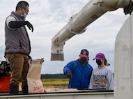 U.S. Air Force Col. Jesse J. Friedel, 35th Fighter Wing commander, speaks with his daughter about the rice harvesting process during a community relations event in Misawa City, Japan, Oct. 8, 2020. While rice can now be harvested using a machine, Misawa Mayor Yoshinori Kohiyama, Friedel and his family, and Oozora Elementary School students harvested rice by hand. (U.S. Air Force photo by Tech. Sgt. Timothy Moore)