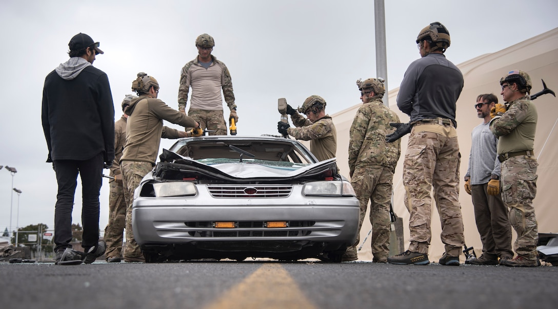 Oregon Air National Guard pararescuemen and combat controllers from the 125th Special Tactics Squadron, along with training instructors, conduct extrication training at Portland Air National Guard Base, Portland, Ore., Oct. 8, 2020. The members used a combination of tools to open up non-salvageable vehicles in order to simulate removing trapped personnel. (U.S. Air National Guard photo by Senior Airman Valerie R. Seelye)