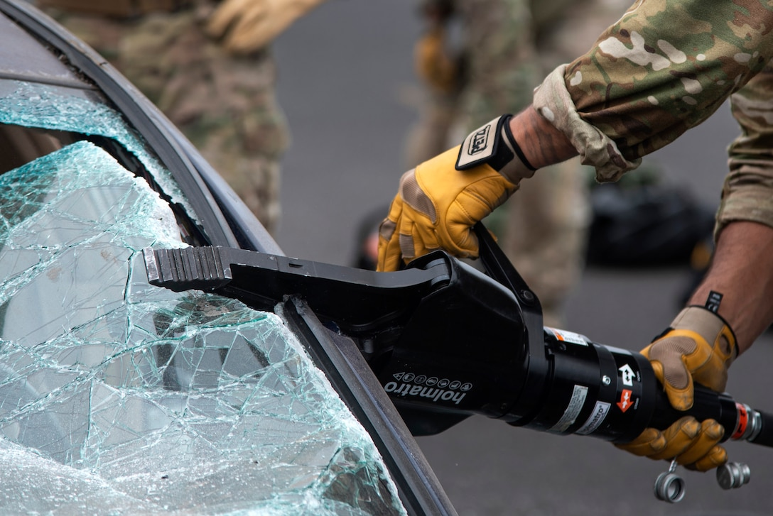 """An Oregon Air National Guardsman from the 125th Special Tactics Squadron, uses a tool called the """"jaws of life"""" to conduct extrication training at Portland Air National Guard Base, Portland, Ore., Oct. 8, 2020, to simulate removing trapped personnel from a car or aircraft. The training allowed members to utilize specialty tools in a controlled environment. (U.S. Air National Guard photo by Senior Airman Valerie R. Seelye)"""