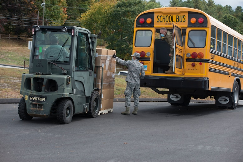 Members of the Connecticut Air National Guard, 103rd Logistics Readiness Squadron, load Farmers to Families Food Boxes onto a school bus at the Killingly Highway Department in Dayville, Connecticut, Sept. 30, 2020. The boxes were going to be delivered to homes and food pantries.