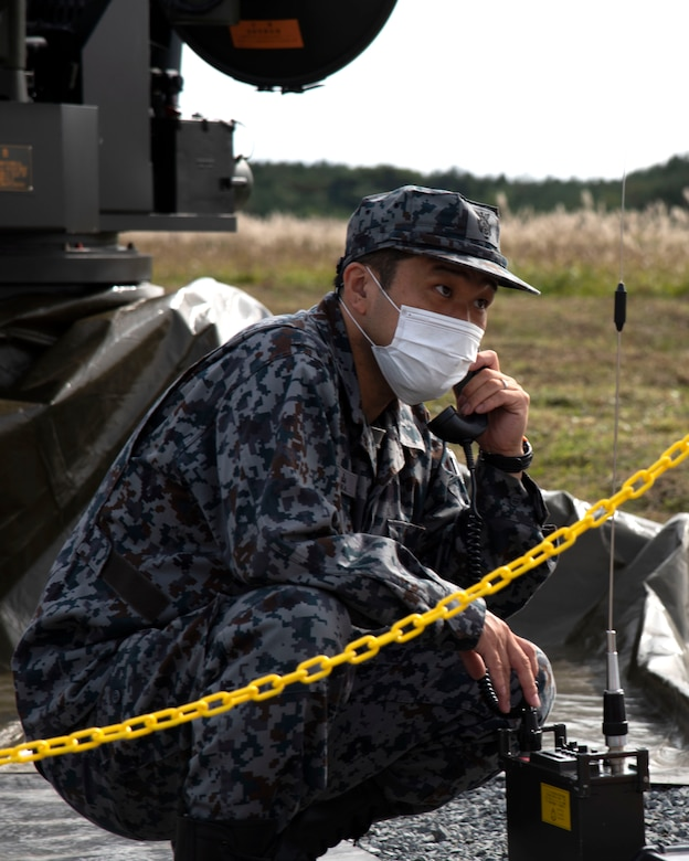 A man in uniform kneels outside while talking on a corded phone