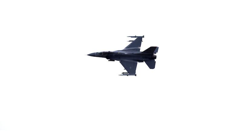 A grey aircraft flies sideways through a clear sky