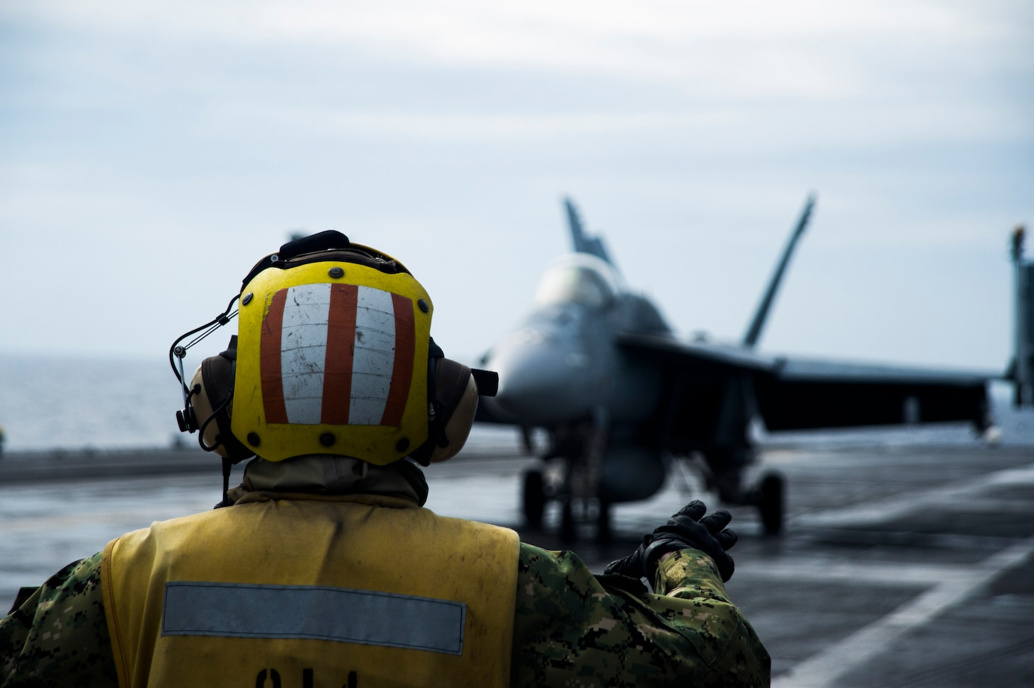 "Aviation Boatswain's Mate (Handling) 1st Class Keyonnia Cook, from Augusta, Georgia, signals to the pilot of an F/A-18E assigned to the ""Eagles"" of Strike Fighter Squadron (VFA) 115 aboard the aircraft carrier USS Ronald Reagan (CVN 76) while conducting security and stability operations in the South China Sea. Ronald Reagan, the flagship of Carrier Strike Group 5, provides a combat-ready force that protects and defends the U.S. as well as the collective maritime interests of its allies and partners in the Indo-Pacific."