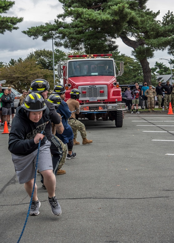 Participants pull a fire truck during the 2020 Fire Muster at Misawa Air Base, Japan, Oct. 6, 2020. The muster is a culmination of fun events designed to bring the community and firefighters together to promote prevention of fire mishaps through education. Fire musters give Airmen from different career fields across the wing an opportunity to test their fitness abilities against one another while experiencing tasks a firefighter would conduct during an emergency. (U.S. Air Force photo by Airman 1st Class China M. Shock)