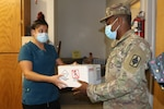 Jessica Robinson, Doniphan County Health Department and Home Health office manager, transfers a box of COVID-19 test samples to Spc. Adrian Turner, Kansas Army National Guard automated logistical specialist, 997th Brigade Support Battalion, in Troy, Kansas, July 27, 2020. Kansas National Guard teams have been transporting COVID-19 samples from across the state to the KDHE lab since March.